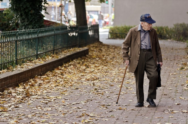 elderly man walking with cane