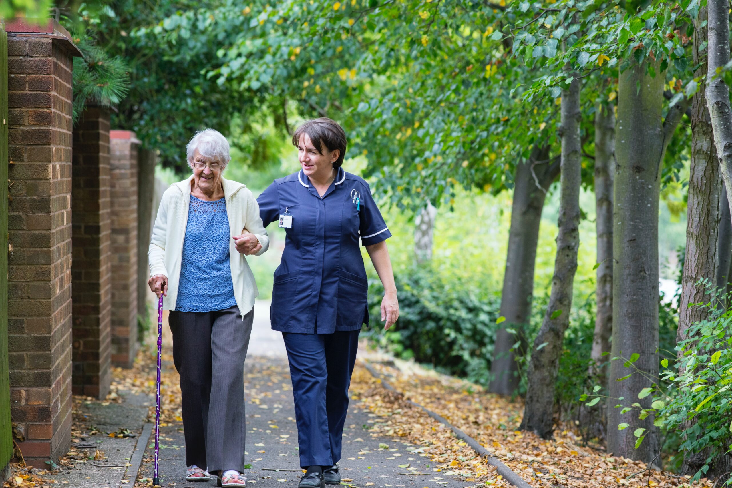Elderly Woman Walking with Caregiver