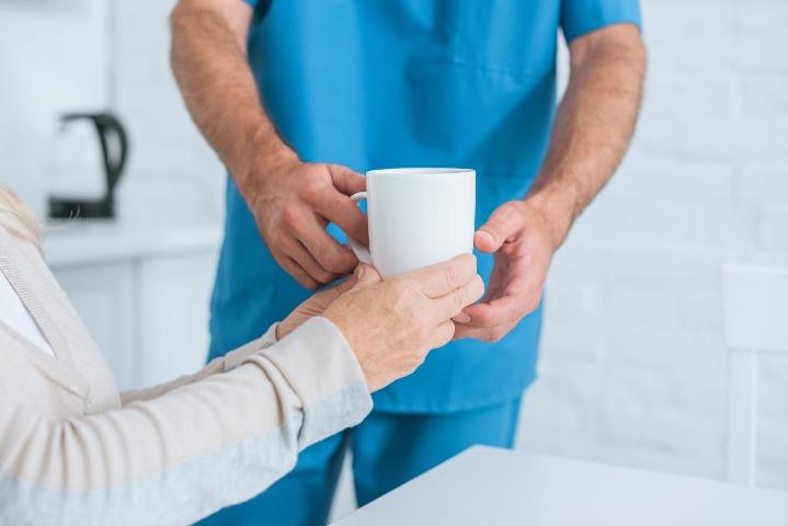 Caregiver Giving Patient Some Tea